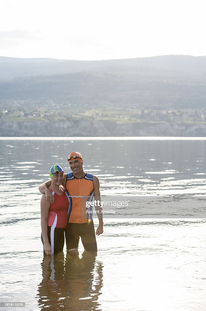 Father & daugter triatheletes portrait, lake : Stock Photo