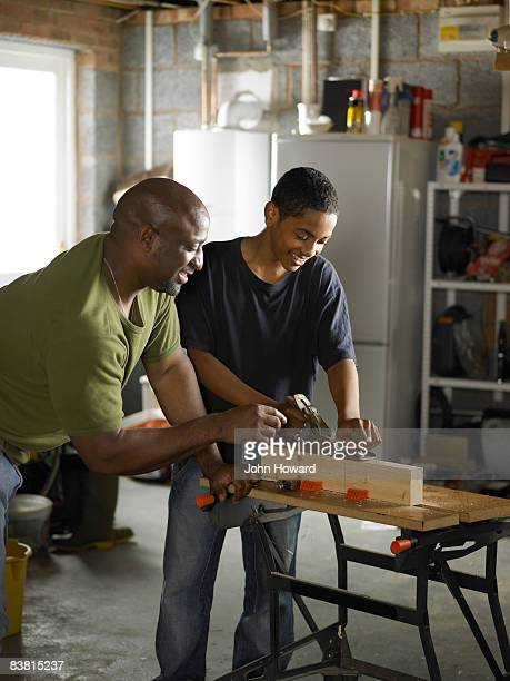 Father demonstrating carpentry skills to Son