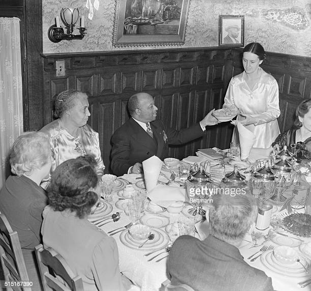 Father Divine a famous African American spiritual leader and his wife Sister Penny sit at the head of a lavish and festive dining table as they enjoy...