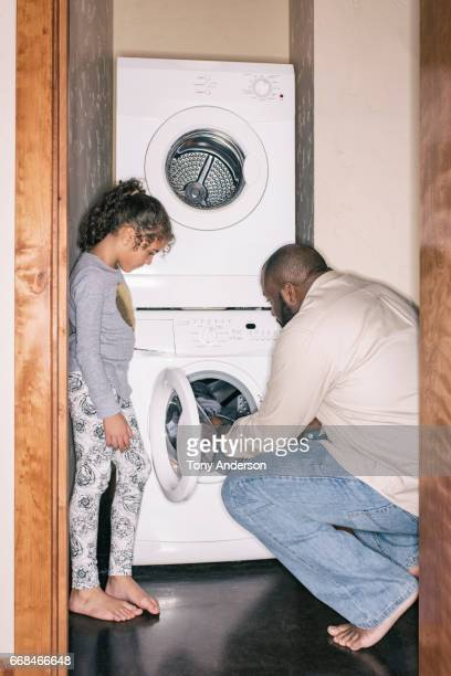 Father doing the laundry with his daughter