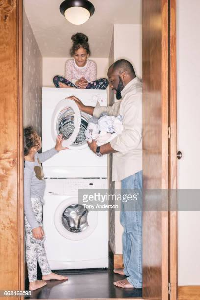 Father doing the laundry with his twin  daughters