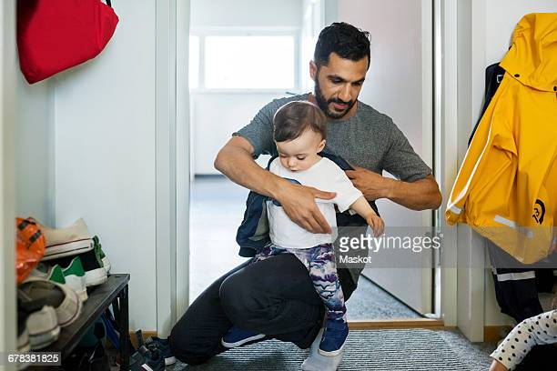 Father dressing daughter while crouching at doorway