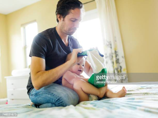 Father dressing son (12-17 months) in bedroom