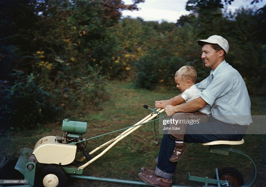 Father driving riding lawnmower with son (21-24 months)  on lap : Stock Photo