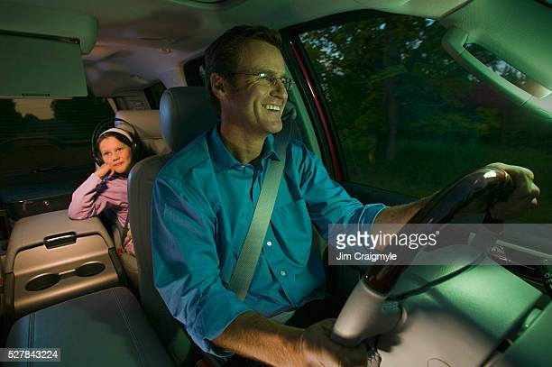 Father Driving While Daughter Watches DVD