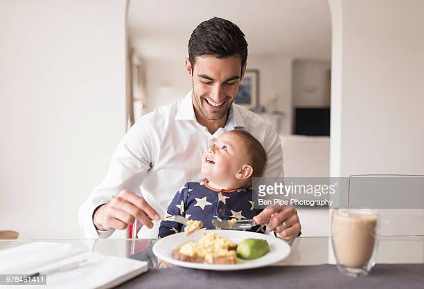 Father eating meal with young son sitting on his lap
