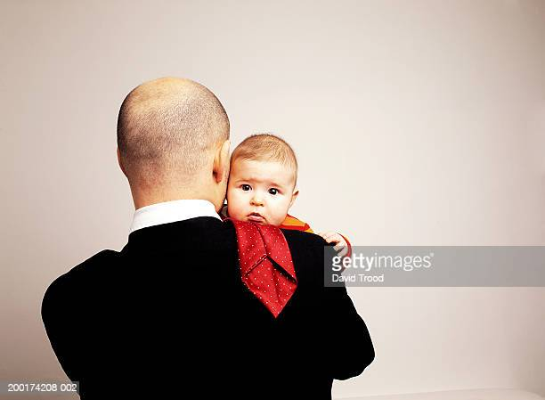 Father embracing baby girl (6-9 months), rear view of man