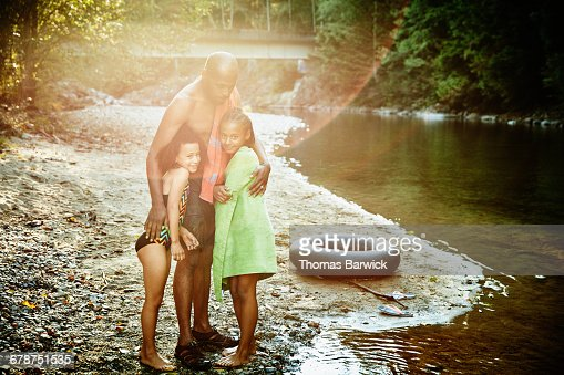 Father embracing daughters by river after swim