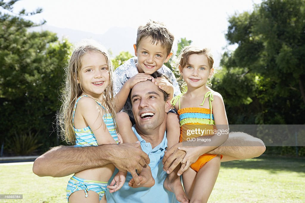 A father embracing his three young children : Stock Photo