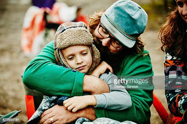 Father embracing young son while camping