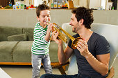 Father encouraging young son playing trumpet