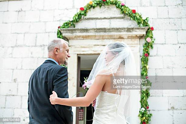Father escorting bride to church, rear view
