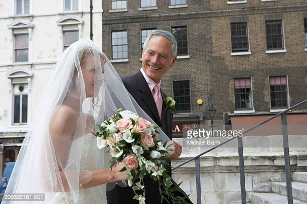 Father escorting bride up steps to church, smiling, close-up
