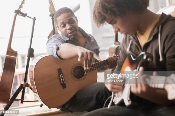 Father explaining electric guitar to teenager