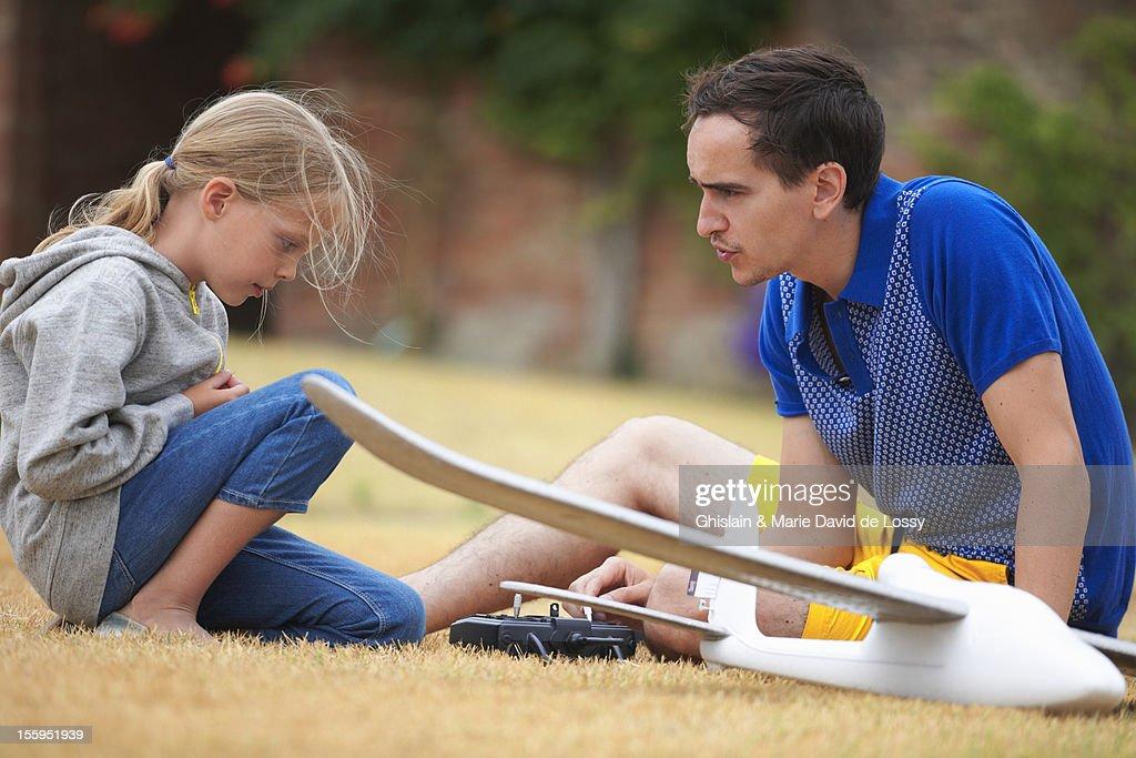 Father explaining to daughter how RC plane works : Bildbanksbilder