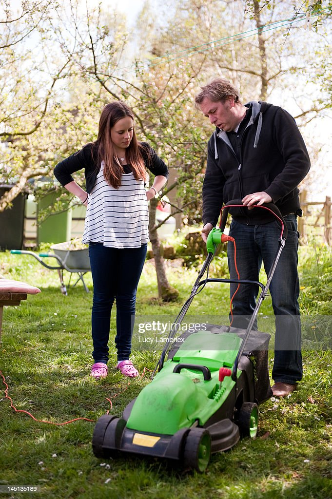 Father explaining to daughter with lawnmower : Stock Photo