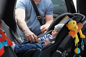 Father fasten his little son in car seat. The concept of security.