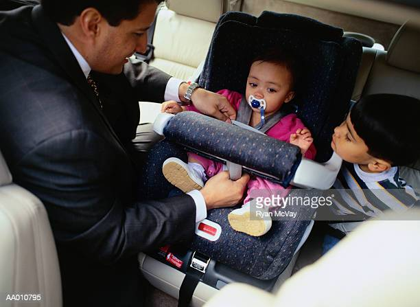 Father Fastening His Daughter in a Car Seat