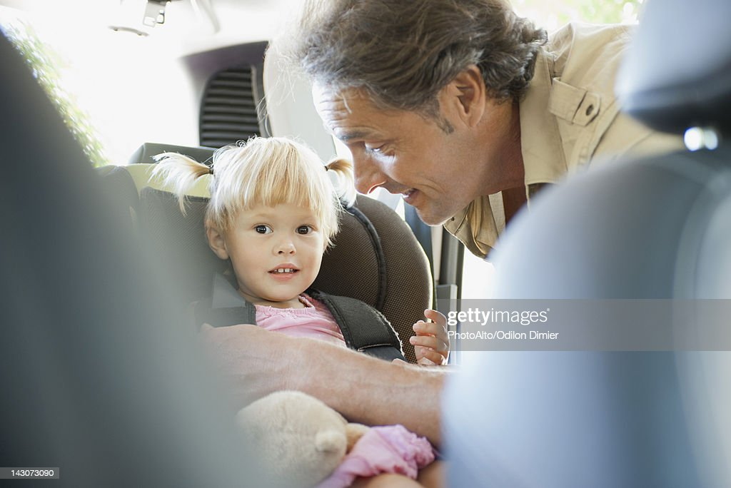 Father fastening little girl into car seat : Stock Photo