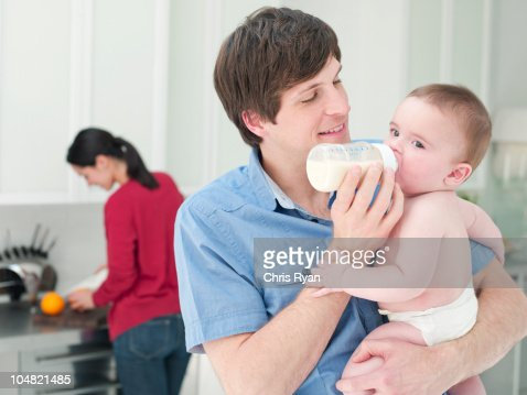 Father feeding baby bottle of milk : Stock Photo