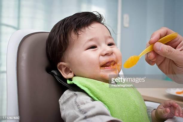 Father feeding baby boy in a highchair