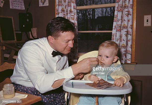 Father feeding baby boy (12-15 months) sitting in highchair