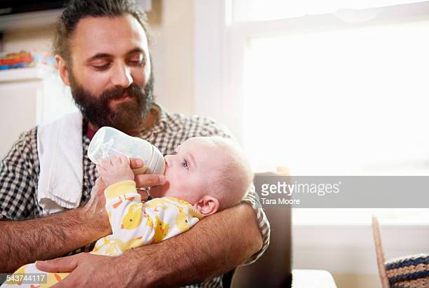 Father feeding baby in arm with bottle at home