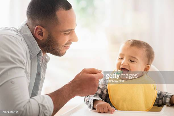Father feeding baby son in high chair