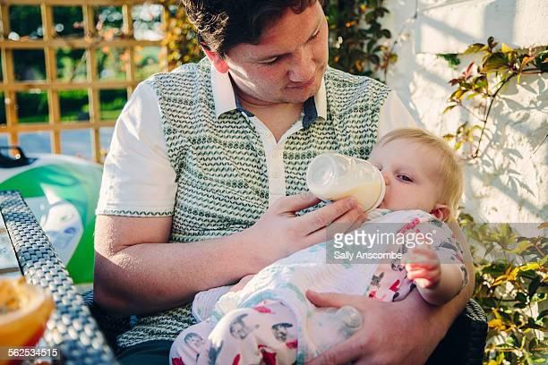 Father feeding his baby girl