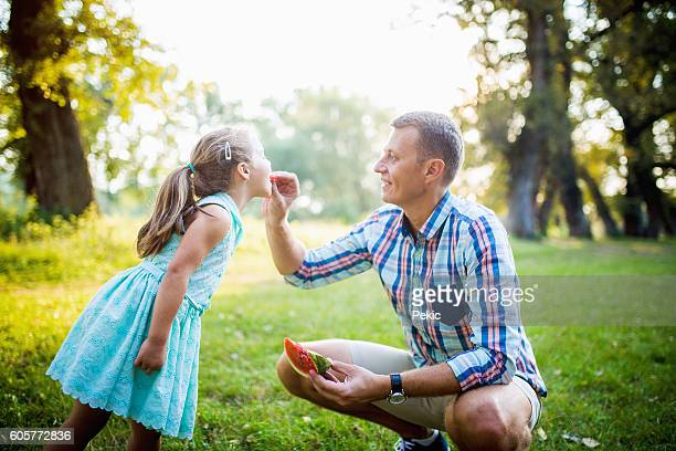 Father feeding his daughter with watermelon