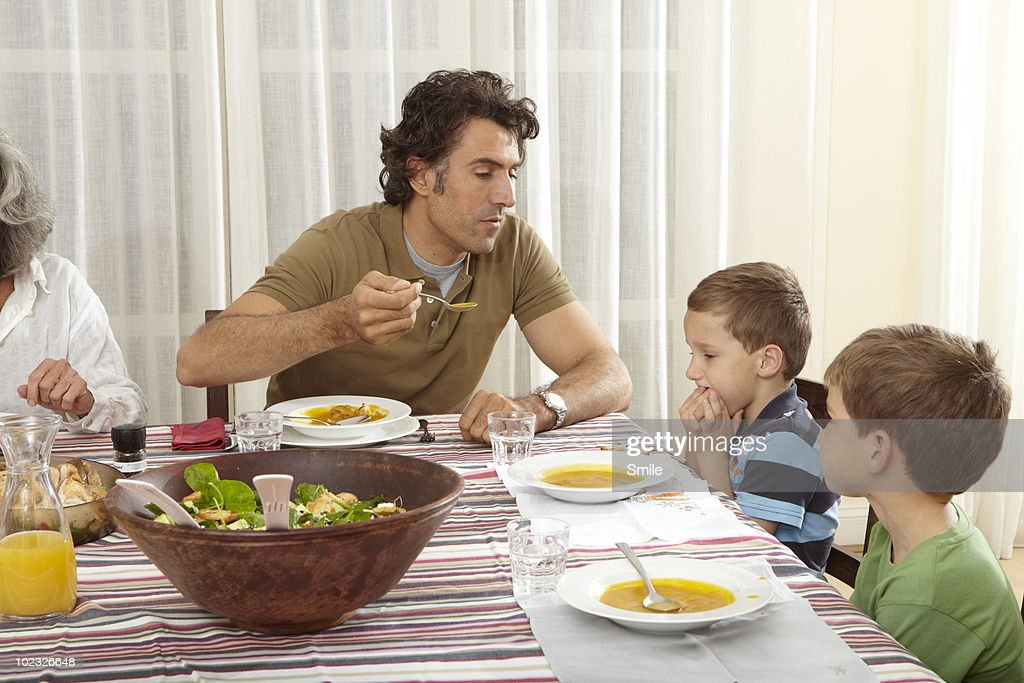Father feeding his son soup, son refusing : Stock Photo