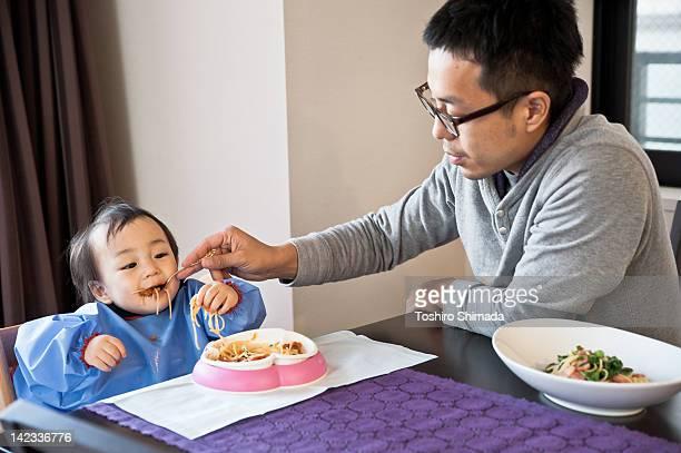 Father feeding small kid