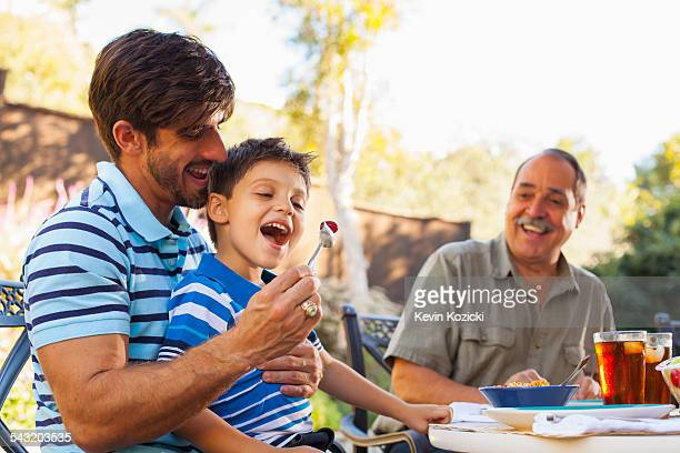 Father feeding son on lap, grandfather in background