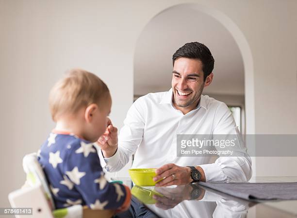 Father feeding young son, indoors