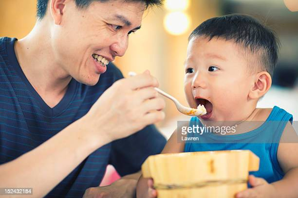 Father feeds boy with big wooden bowl