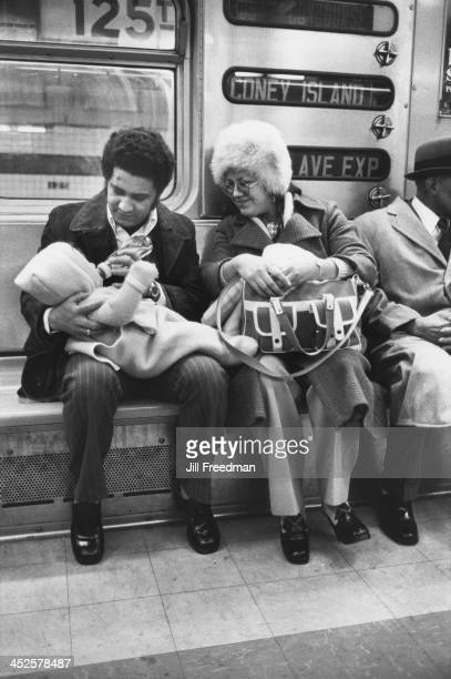 A father feeds his baby on a subway train New York City 1977