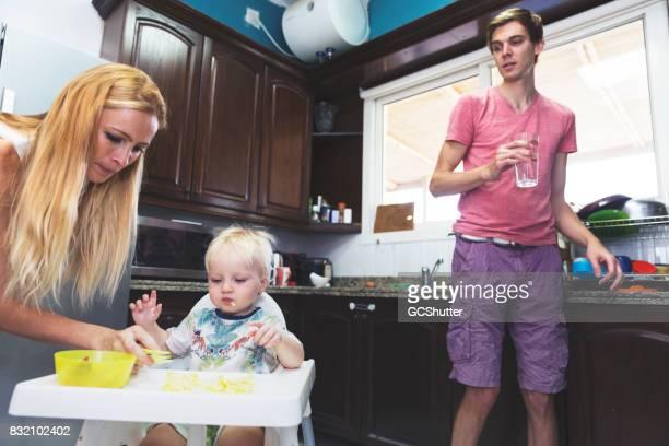 Vater ein Glas Wasser zu holen, während die Frau die Babynahrung ernährt