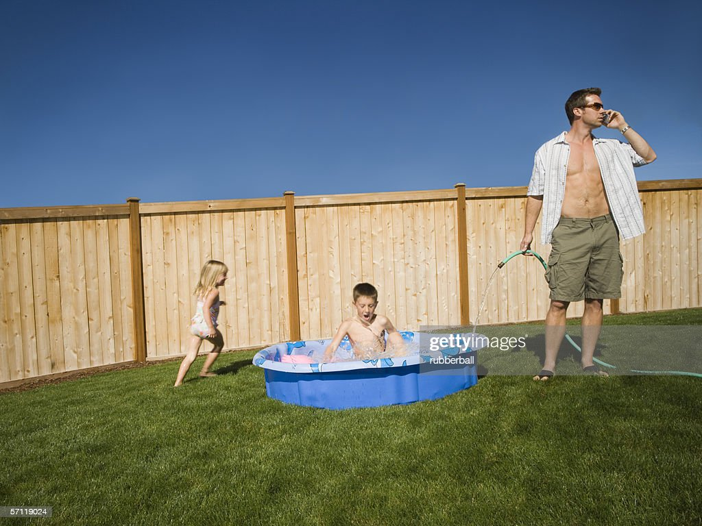 father filling up a wading pool stock photo getty images