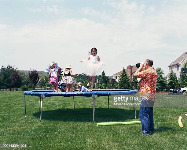 Father filming children (2-12) playing on trampoline on lawn