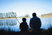 Father fishing with son in lake