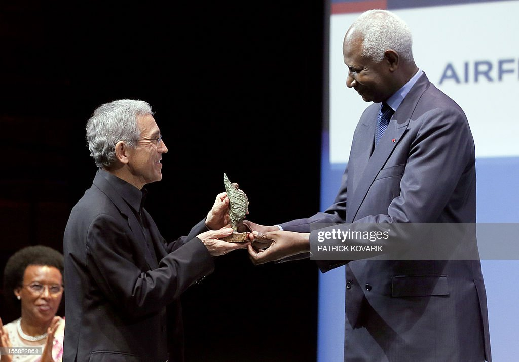 Father Francisco de Roux (L) is awarded by Secretary General of the International Francophonie Organization (OIF), Abdou Diouf for the prize for conflict prevention during the ceremony of release of the Jacques Chirac Foundation's 2012 Award for the prevention of conflicts, on November 22, 2012 at the Quai Branly Museum in Paris. AFP PHOTO PATRICK KOVARIK