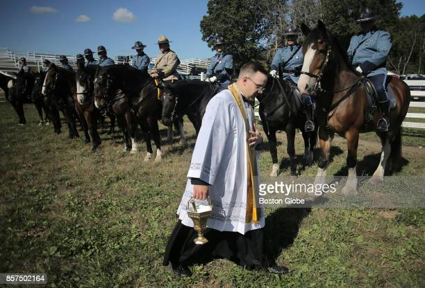 Father Frederick Fraini a State Police chaplain blesses horses and dogs from the Massachusetts State Police Plymouth County Sheriff and Boston Park...