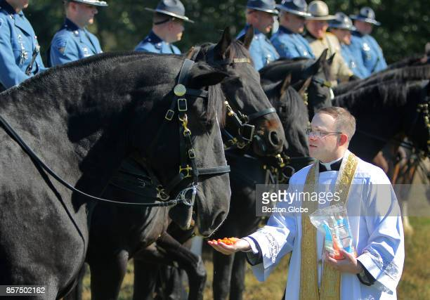 Father Frederick Fraini a State Police chaplain gives a carrot snack to all the horses after blessing horses and dogs from the Massachusetts State...