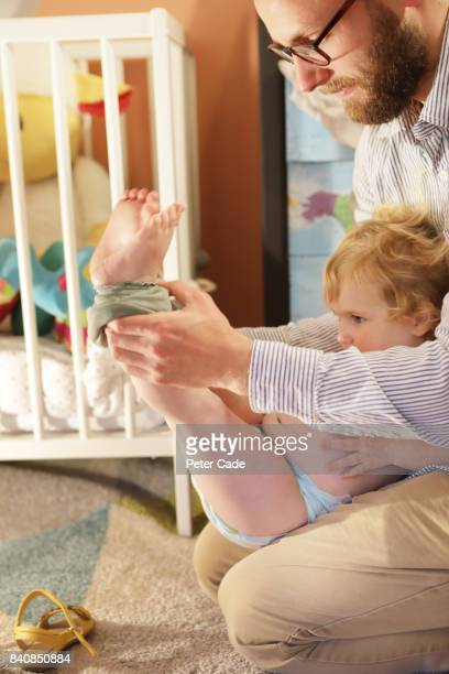 Father getting toddler undressed in bedroom
