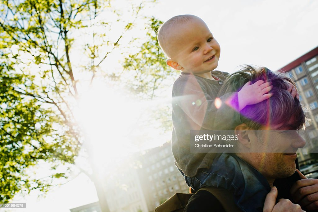 Father giving baby daughter shoulder ride whilst walking in city