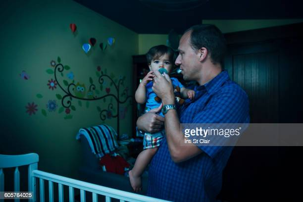 Father giving baby son pacifier in nursery