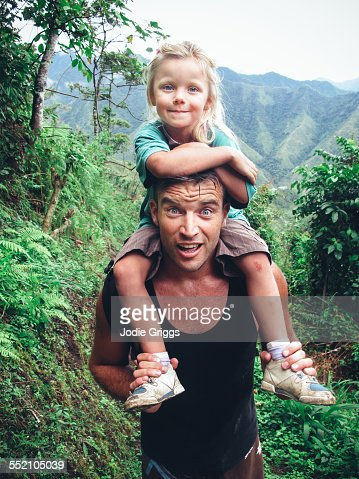 Father giving child a shoulder ride whilst hiking