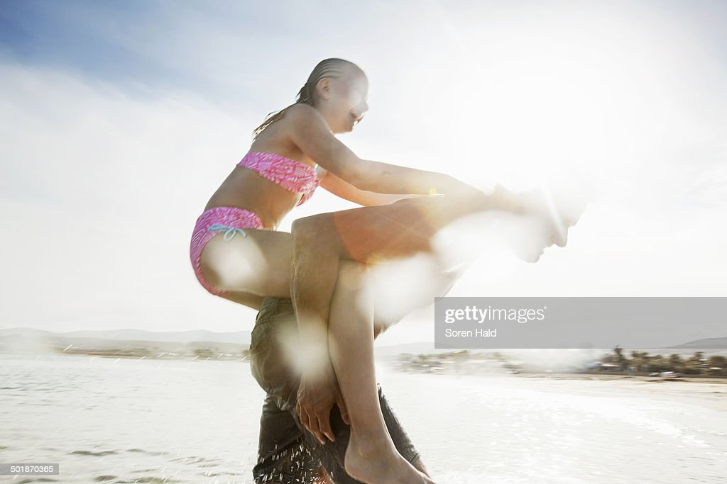 Father giving daughter piggy back on beach