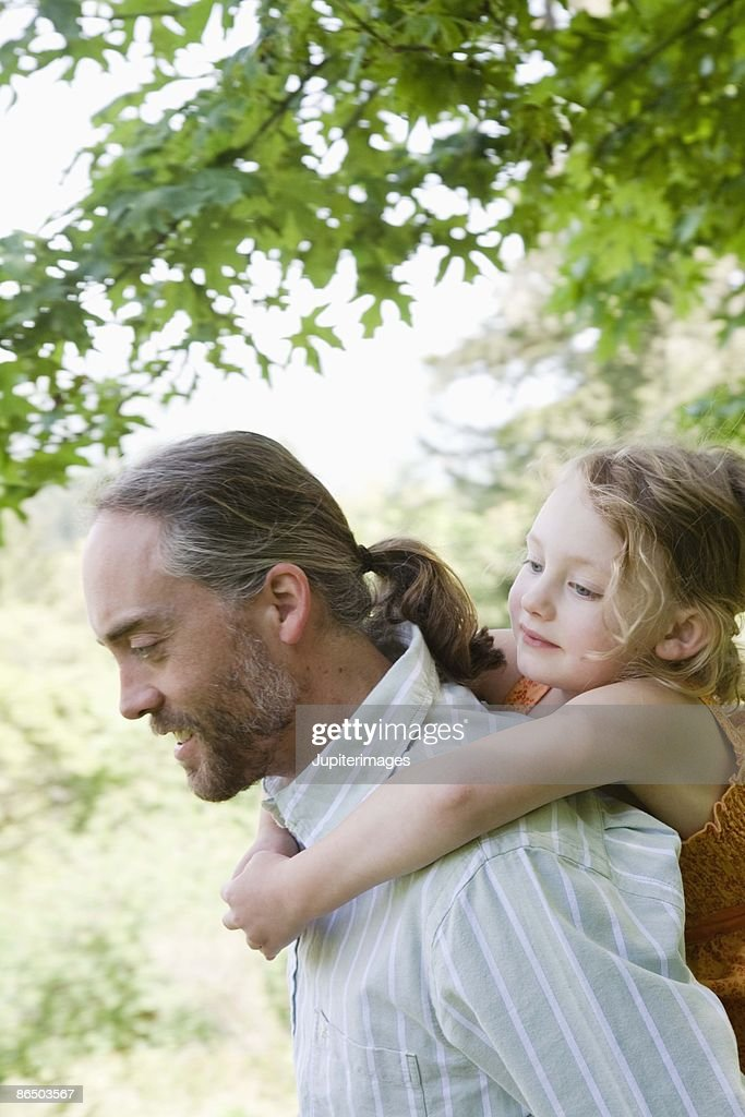 Father giving daughter piggyback ride : Stock Photo