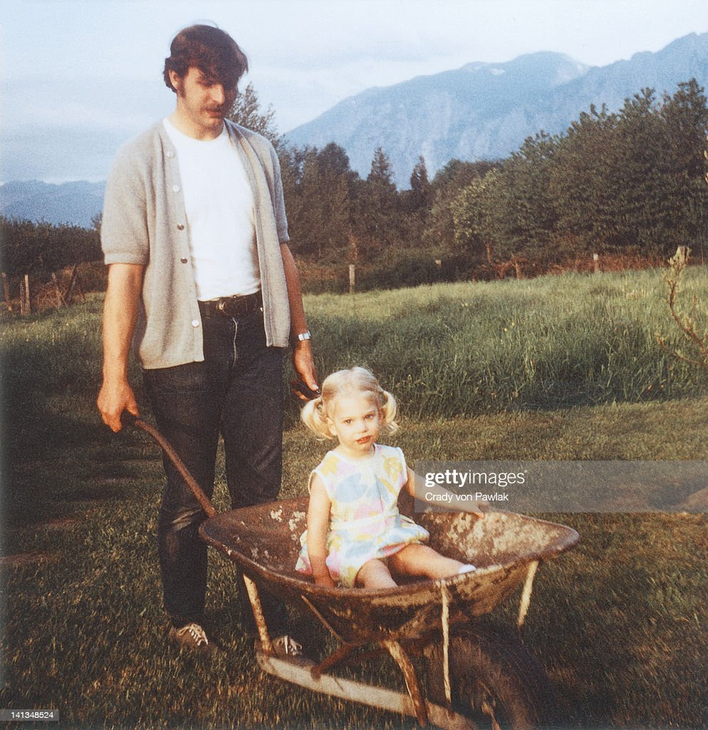 Father giving daughter wheelbarrow ride : Stock Photo